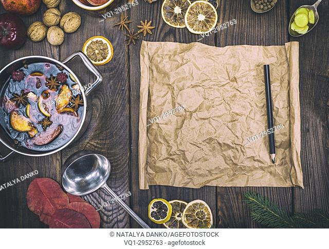 empty brown paper scroll and black pencil in the middle of the ingredients for mulled wine, vintage toning