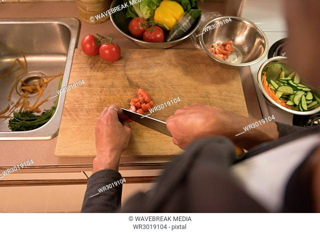 Man chopping tomato on cutting board