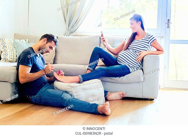 Man pampering pregnant woman on sofa