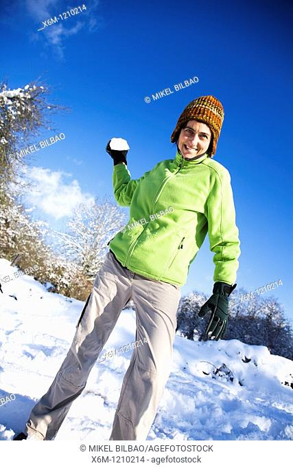 young woman playing with snowballs in a snow covered landscape