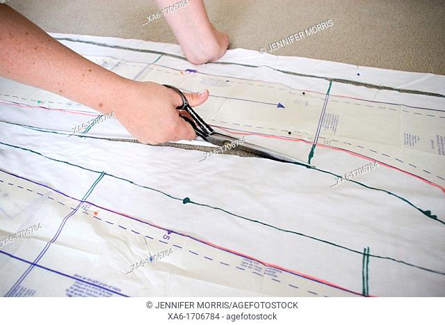 A woman cuts fabric that a dress pattern is pinned to