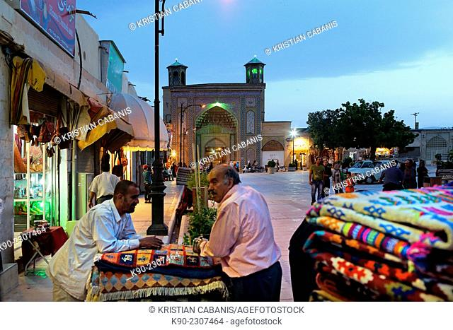 Two carpet dealer standing outside off their shop with the buildings of the souq in the background, Shiraz, Iran, Asia