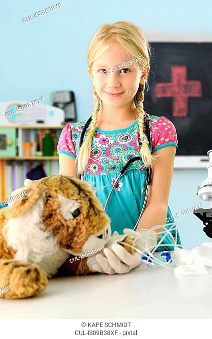 Portrait of girl pretending to be vet to toy tiger with intravenous drip