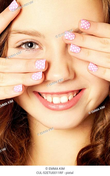Smiling girl with polka dot manicure