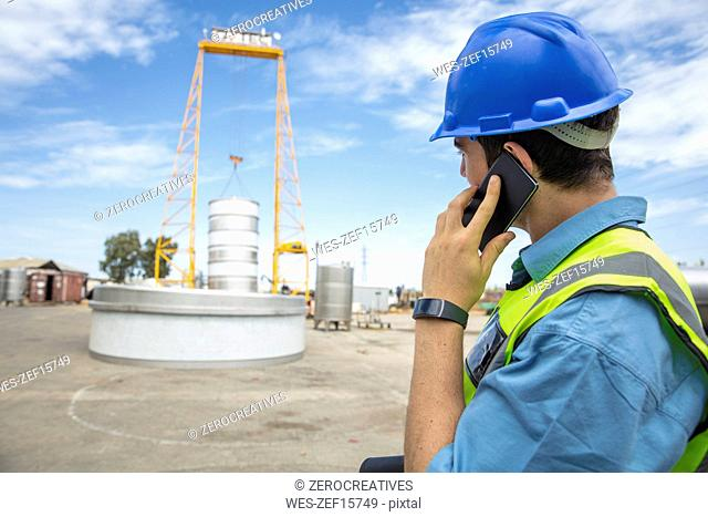 Man in workwear on construction site talking on cell phone
