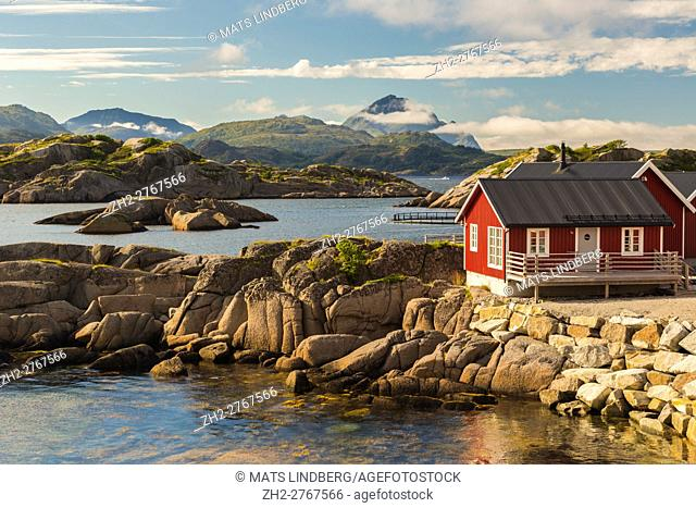 Rorbuer in nice warm evening light, clouds over the mountains in the background, Mortsund, Lofoten Islands, Norway