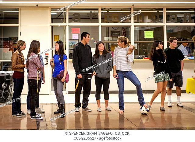 Multiracial high school students converse on campus in Mission Viejo, CA