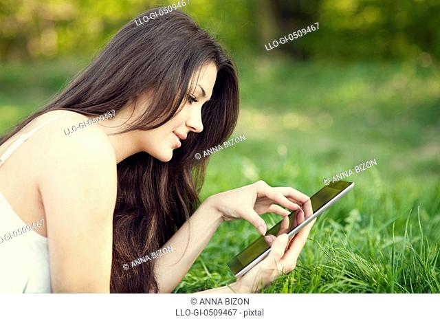 Young woman using digital tablet on meadow Debica, Poland