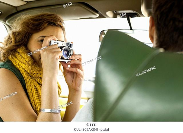 Young woman photographing boyfriend driving, Cape Town, Western Cape, South Africa