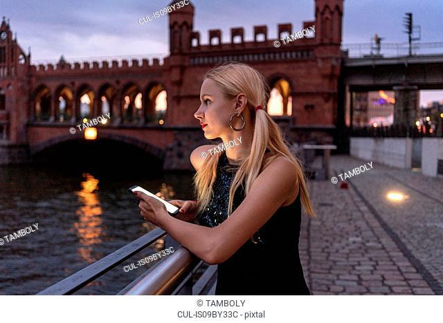 Hipster woman by riverside, Berlin, Germany