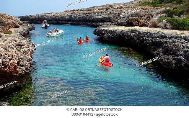 Tourists in a kayak in Cala Estreta, a small bay in the municipality of Felanitx, Majorca island, Spain, Europe