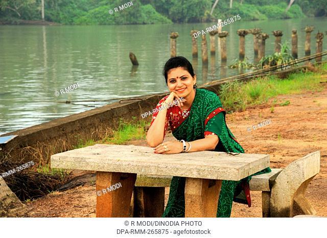 woman sitting stone table chair, isola di cocco, Kerala, India, Asia, MR#802B