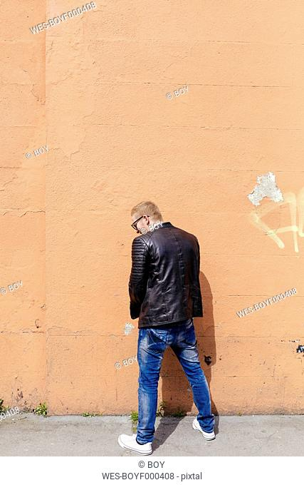 Back view of young man peeing at facade