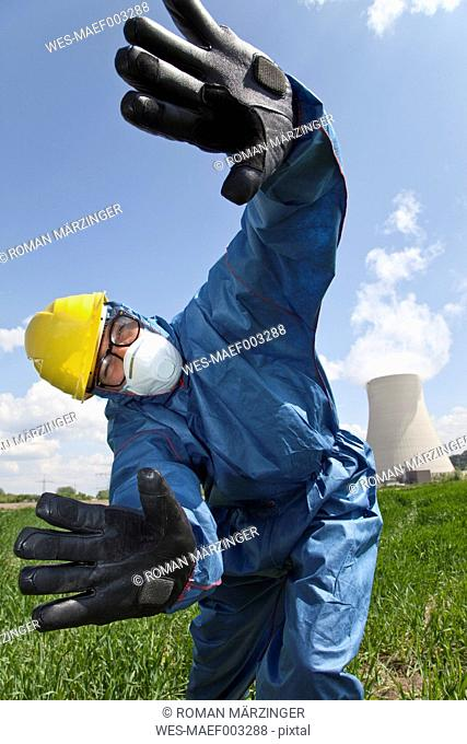 Germany, Bavaria, Unterahrain, Man with protective workwear gesturing in field at AKW Isar