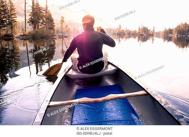 Young man canoeing on Echo Lake, rear view, High Sierras, California, USA