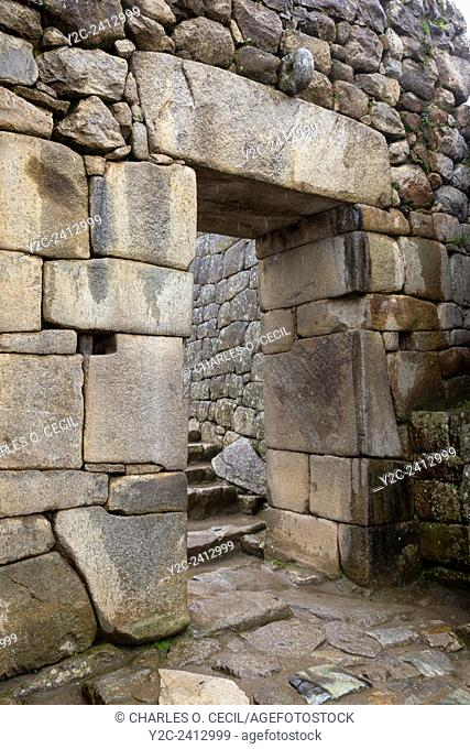 Peru, Machu Picchu. Inside Main Gate into the City. The hole in the circulart stone above the door and the chest-high opening on either side served to brace a...