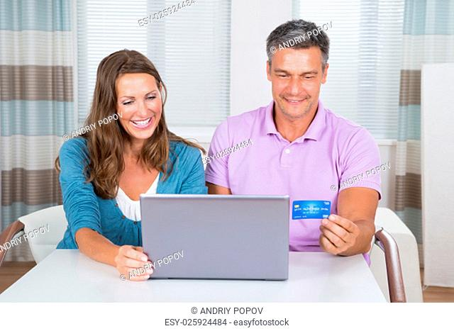 Smiling Couple Sitting In Living Room Shopping Online On Laptop