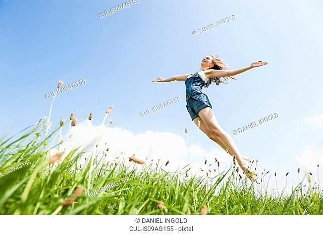 Woman jumping in midair with arms open