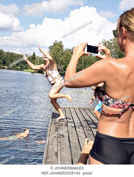 Happy woman on jetty, girl taking picture