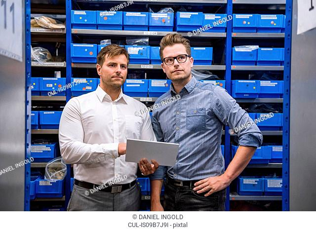 Two male managers using digital tablet for stock taking in factory warehouse