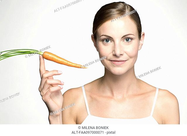 Young woman holding up raw carrot