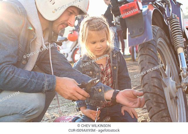 Man fixing wheel on moped, daughter watching
