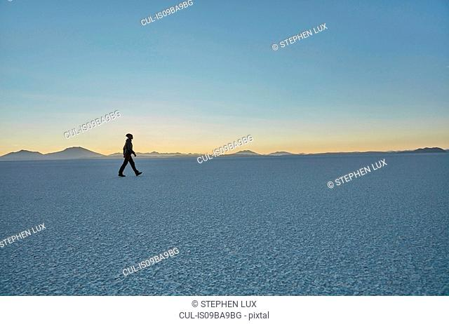 Woman walking across salt flats, Salar de Uyuni, Uyuni, Oruro, Bolivia, South America
