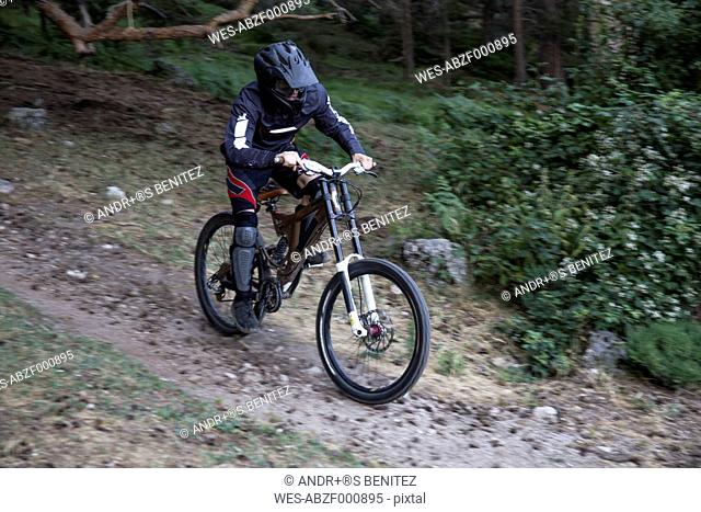 Mountainbiker riding downhill on forest path
