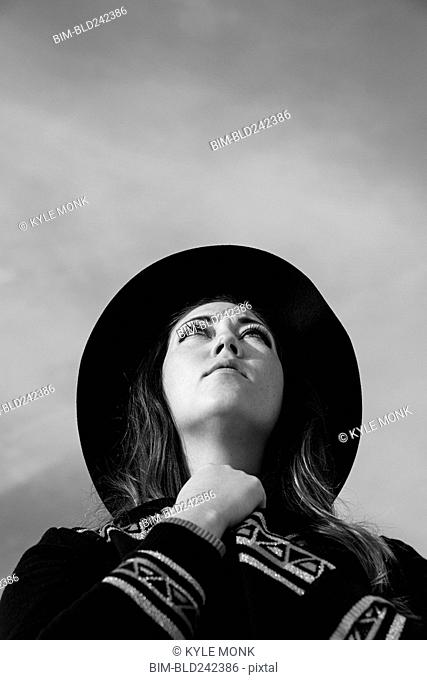Caucasian woman wearing hat looking up