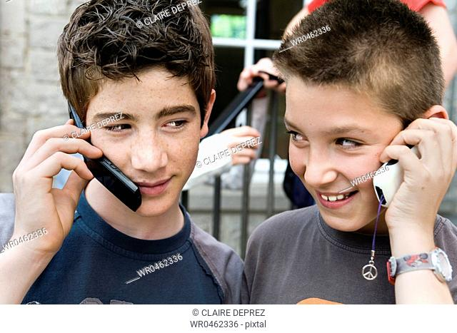 Close-up of two teenage boys talking on mobile phones