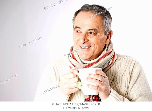 Friendly elderly man wearing a scarf and holding a cup of tea