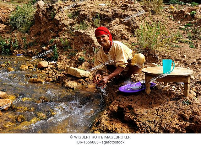 Elderly Berber woman cleaning dishes in a stream, Middle Atlas, Morocco, Africa