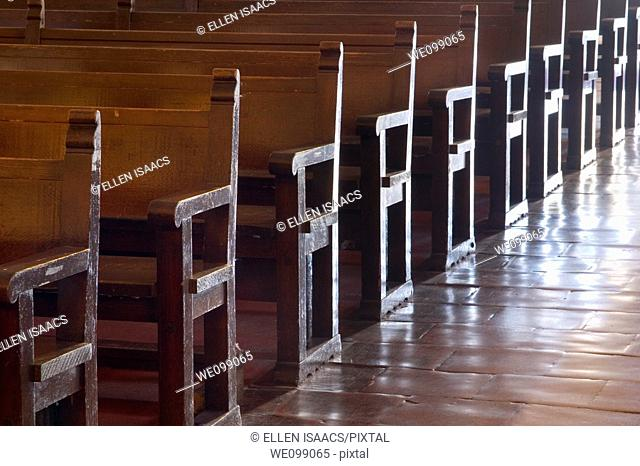 Rows of wood pews for worship in the Carmel Mission Basilica church Mission San Carlos Borromeo del Rio Carmelo in Carmel, California