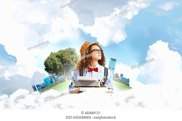 Young and beautiful woman writer in hat and eyeglasses using typing machine while sitting at the table with floating city island and cloudy skyscape on...