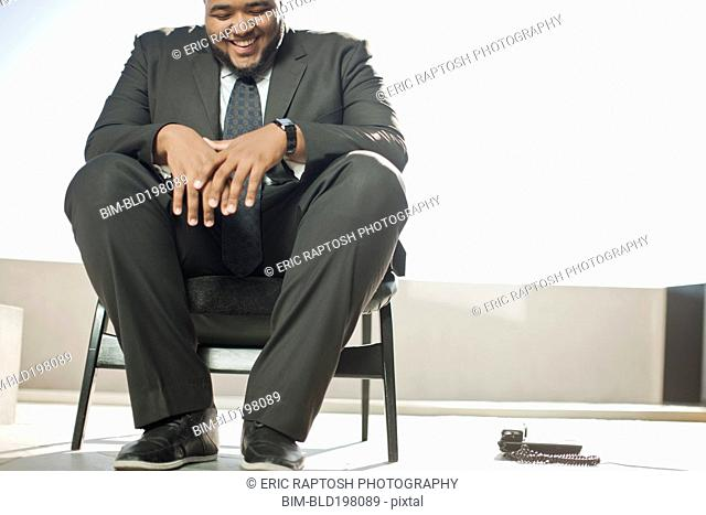 Smiling mixed race businessman sitting on patio