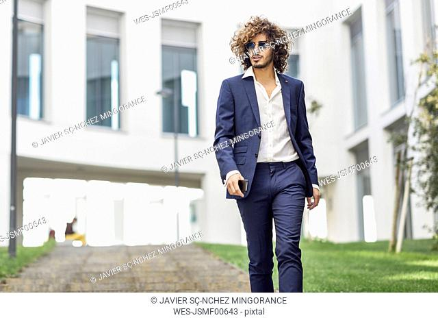 Portrait of young fashionable businessman with curly hair wearing blue suit and sunglasses