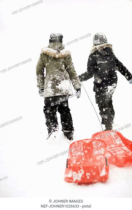 Sweden, Stockholm, rear view of two girls (8-9) walking with toboggans in snow