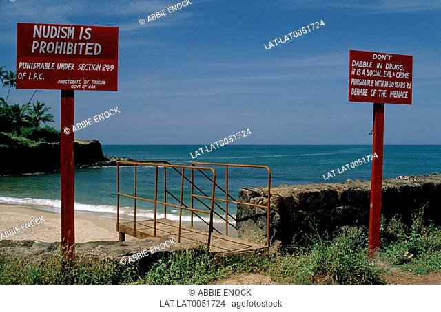 Warning signs on a beach saying 'Nudism is prohibited' and warnings about drug use