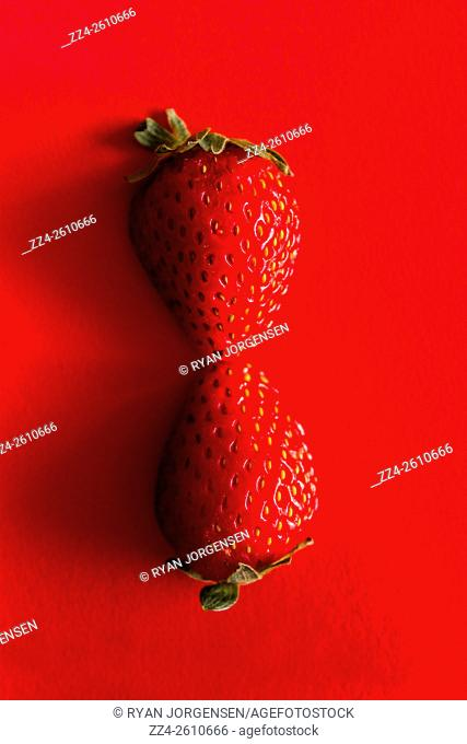 Sliced strawberry placed symmetrically in self reflection on red background. Sweet parallels