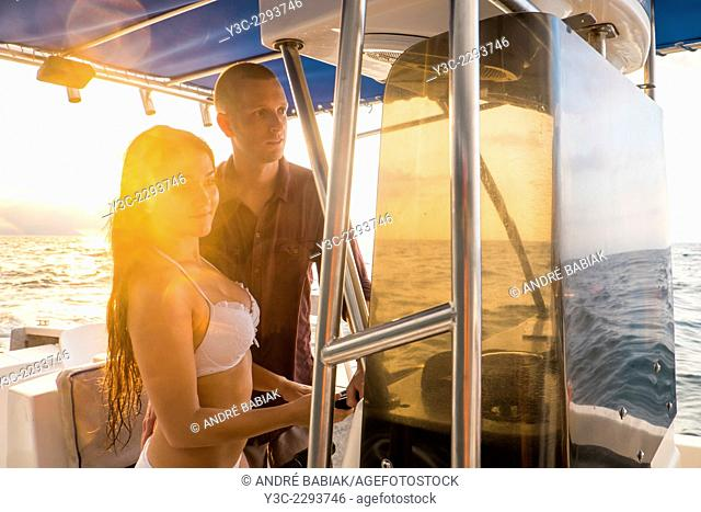 Young man and woman, caucasian ethnicity, are steering their fishing boat at sea. Time of day is right befor sunset