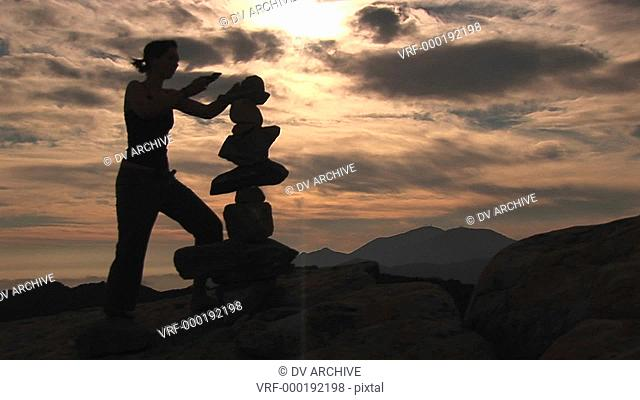 Medium-shot of a silhouetted woman stacking rocks on a mountaintop