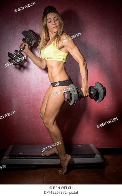 A woman lifting free weights; Tarifa, Cadiz, Andalusia, Spain