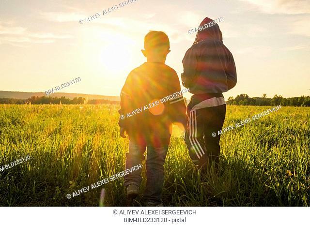 Mari boys walking in field at sunset