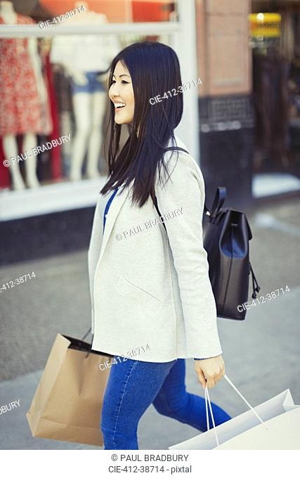 Smiling young woman walking along storefront with shopping bags