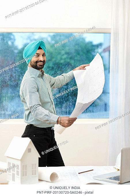 Architect holding a blueprint and smiling