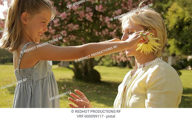 grandmother and granddaughter playing with flower in park