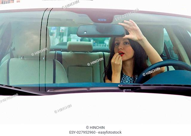 Cute brunette with red lips painting lips inside luxury white car (Jaguar XF)