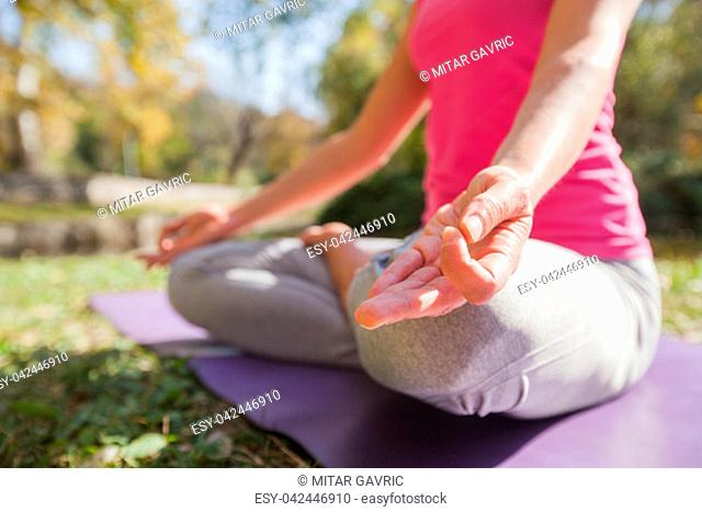 Woman Meditating And Practicing Yoga At Park On Beautiful Sunny Autumn Day