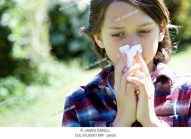 Boy blowing his nose outdoors