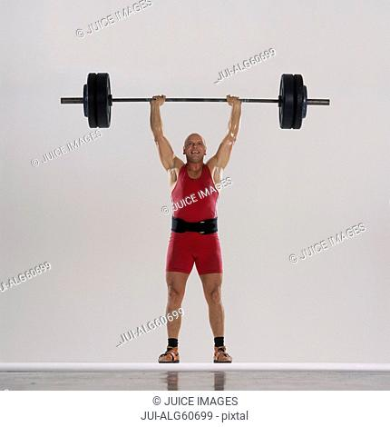 Bald-headed weightlifter lifting barbell
